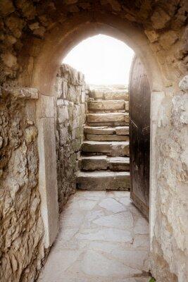 Fototapeta Ściana z kamienia z otwartymi drzwiami i promieni światła z tyłu