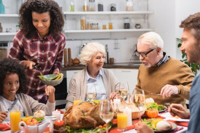 Fototapeta selective focus of joyful african american woman serving vegetables during festive dinner on thanksgiving day