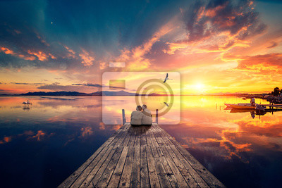 Fototapeta Senior couple seated on a wooden jetty, looking a colorful sunset on the sea with a flying flamingo reflected on the calm water.