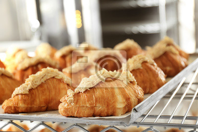 Fototapeta Shelf with delicious sweet croissants on tray in bakery