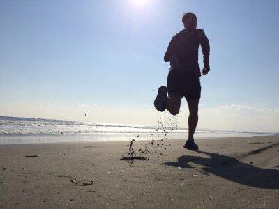 Fototapeta Silhoette człowieka działa na plaży