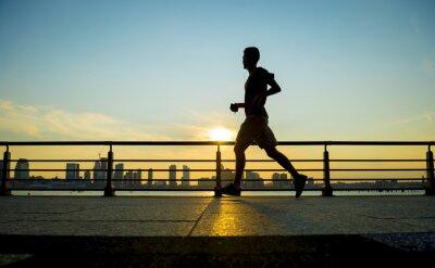 Fototapeta Silhouette of jogger running at sunset in front of the city skyline