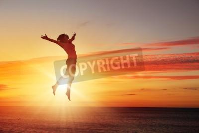Fototapeta Silhouette tancerz skoków przeciwko miastu w? Wietle wschodu s? O? Ca