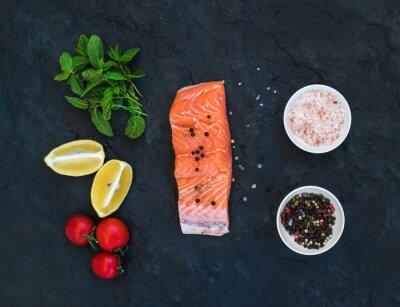 Fototapeta Składniki. Surowy filet z łososia, z cytryny, pomidory cherry, świeżej mięty i przypraw na ciemnym tle kamienia