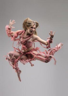 Fototapeta Skoki swathed kobieta w studio na szarym tle