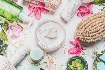 Fototapeta Skóry śmietanka z kwiatów płatkami i inny ciało dbamy kosmetycznych produkty i akcesoria na białym tle, odgórny widok