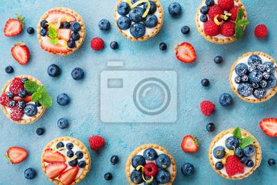 Fototapeta Smakowite tartaletki jagodowe lub ciasto ze śmietaną i różnymi jagodami. Ciasto deserowe widok z góry.