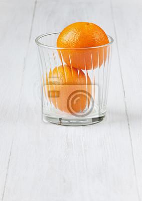 Soczyste mandarynki w szklance na białym powierzchni drewnianych