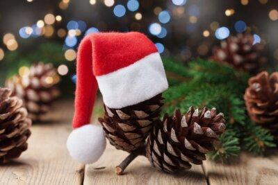 Sosna rożek dekorował Santa kapelusz i jedlinową gałąź na nieociosanym tle. Bożenarodzeniowy kartka z pozdrowieniami.