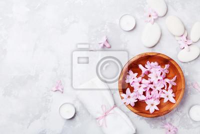 Spa, aromaterapia, tło uroda z kamykiem do masażu, perfumowane kwiaty wody i świece na stole z kamienia z góry. Relaks i zen jak koncepcja. Płaskie leżało.