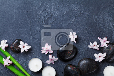 Spa background with massage pebble, green leaves, beautiful flowers and candles on black stone table top view. Aromatherapy, relaxation and zen like concept.