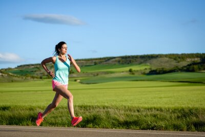 Fototapeta Sporty woman running fast on country side road. Female athlete training outdoor.