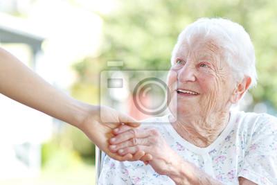Fototapeta Starszy kobieta trzymając się za ręce z opiekunem