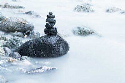 Fototapeta Stos czarnych kamieni w rzece