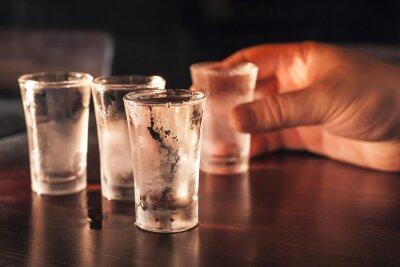 Fototapeta Strzał kieliszek wódki w ręce na drewnianym stole.