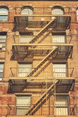 Fototapeta Styl retro zdjęcie budynku z drabiny pożarnicze ewakuacyjnych, NYC.