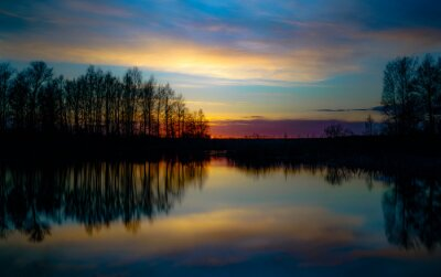 Fototapeta sunset at coast of the lake. Sunset sky. Smooth water