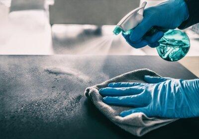 Fototapeta Surface sanitizing against COVID-19 outbreak. Home cleaning spraying antibacterial spray bottle disinfecting against coronavirus wearing nitrile gloves. Sanitize hospital surfaces prevention.