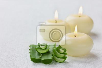 Fototapeta świeży liść aloesu i płonące świece na białej powierzchni