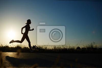 Fototapeta Sylwetka atletyczna dziewczyna uruchomiony w dół drogi do zachodu słońca