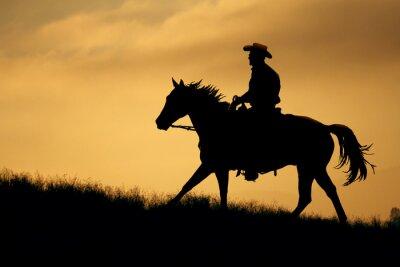 Fototapeta Sylwetka kowboj i koń idzie się łąki z pomarańczowym i żółtym tle nieba.