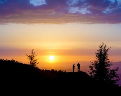 Fototapeta Sylwetki dwóch osób stojących na skale w pobliżu drzewa i patrząc w stronę słońca. Zachód słońca w górach. Lato w Karpatach Ukraińskich