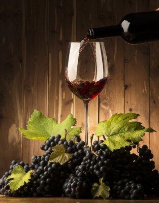 Fototapeta Szkła z czerwonego wina i grapeson drewnianym stole