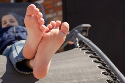 Fototapeta the boy's bare feet on the chaise longue. resting boy in the sun. The concept of relaxation.