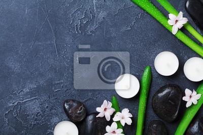 Tło Spa z masażu kamyk, zielone liście, kwiaty i świece na czarny stół z kamienia z góry. Aromaterapia, piękno, relaks i zen jak koncepcja.