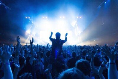Fototapeta Tłum ludzi na koncercie w przód sceny z oświetleniem