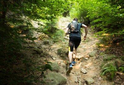 Fototapeta TrailRunner z plecakiem uruchomiony po stromym wzgórzu