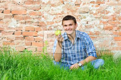 Fototapeta Uśmiecha się młody człowiek z zielonym jabłkiem