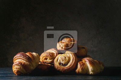 Fototapeta Variety of homemade puff pastry buns cinnamon rolls and croissant on wooden table. Dark still life. Copy space