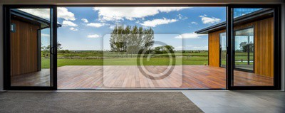 Fototapeta View from a modern house with big glass doors looking at the green field