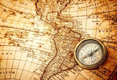 Fototapeta Vintage compass lies on an ancient world map.
