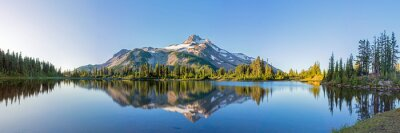 Fototapeta Volcanic mountain in morning light reflected in calm waters of lake.