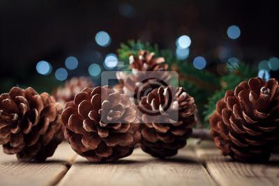 Wciąż życie z sosnowymi rożkami i jedlinową gałąź na nieociosanym drewnianym stole. Bożenarodzeniowy kartka z pozdrowieniami.