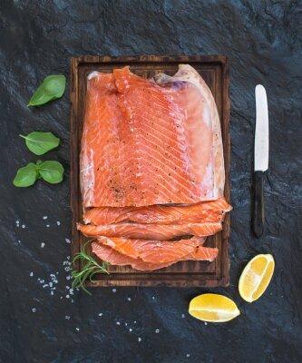 Fototapeta Wędzony filet z łososia z cytryną, świeżych ziół i hodowane na drewnianym pokładzie porcji na ciemnym tle kamienia
