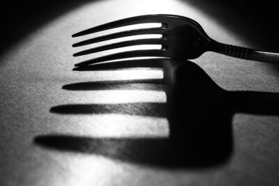 Fototapeta fork on the table in a beam of light with a large shadow