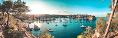 Fototapeta Widok na panoramę zatoki plaży z turkusową wodą i żaglówek i jachtów na kotwicy z ramkami sosny. Piękny romantyczny Cala Portals Vells, Mallorca, Hiszpania. Baleary