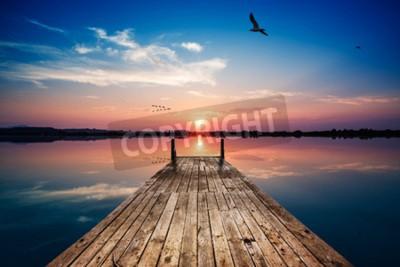 Fototapeta widok perspektywiczny drewnianego molo na stawie o zachodzie słońca, z idealnie zwierciadlanym odbiciem