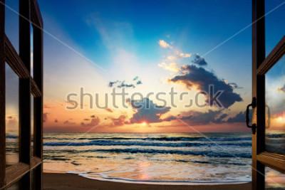 Fototapeta Widok wschodu słońca nad morzem z otwartego okna