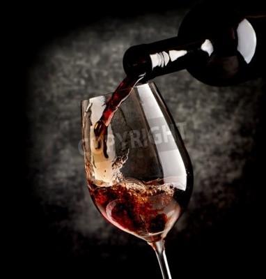 Fototapeta Wino wlewając kieliszka na czarnym tle
