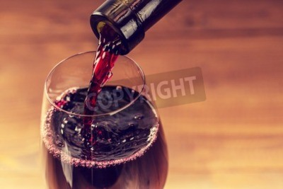 Fototapeta Wlewanie wina czerwonego do szkła przed drewnianym tle