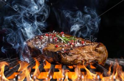 Fototapeta Wołowina stek na grillu w ogieniu z czarnym tłem