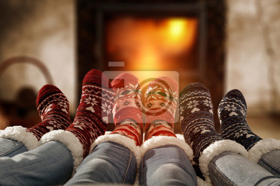 Fototapeta Woman legs in home interior with fireplace.Woolen socks and jeans.Free space for your decoration.Christmas cold winter night.Copy space.