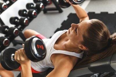 Fototapeta Woman lifting  weights and working on her chest at the  gym