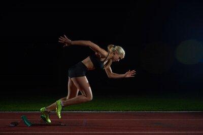 Fototapeta woman  sprinter leaving starting blocks