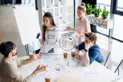 Fototapeta Wysoki kąt widzenia grupy młodych ludzi biznesu omawianie nowego projektu na małe spotkania biznesowe