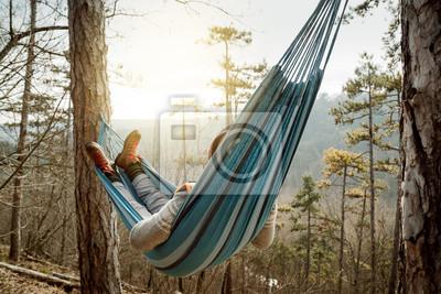 Fototapeta Young happy man relaxing lying in hammock on top of mountain.
